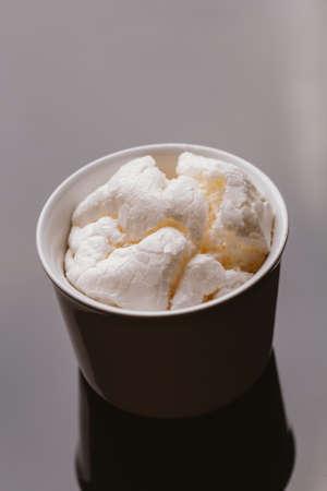 exquisiteness: Fresh meringue in light bowl on a dark background. Stock Photo