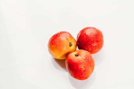 few nectarines on a white mirror background.