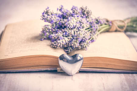 Lavender bouquet laid over  an old book and a silver heart on a white wooden background. Vintage style.