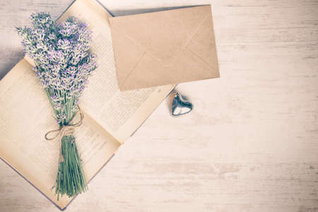 Lavender bouquet laid over  an old book, a silver heart and a kraft paper envelope on a white wooden background. Vintage style.