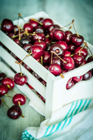 wood crate: Cherries in a white wood crate over a wood background Stock Photo