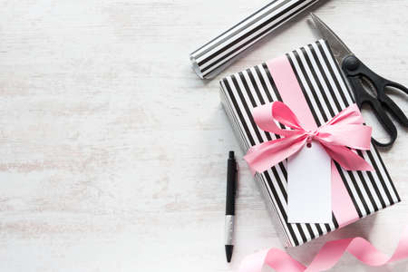 Gift box and wrapping materials on a white wood old background. Greeting note tied over.