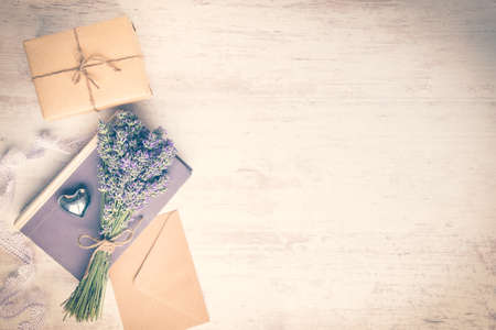 Lavender bouquet laid over  an old book, a wrapped gift box, a kraft paper envelope and a silver heart on a white wooden background. Vintage style.
