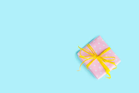 tied in: Top view of a gift box wrapped in pink dotted paper and tied yellow bow over light blue background.