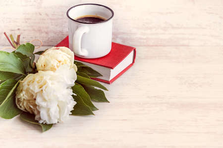 A cup of coffee, white peonies and a red book over a white wooden background.