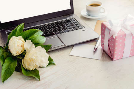 Side view of a deck with computer, bouquet of peonies flowers, cup of coffee, empty card and pink dotted gift box. White rustic wooden background. Romantic and feminine outlook. Stockfoto