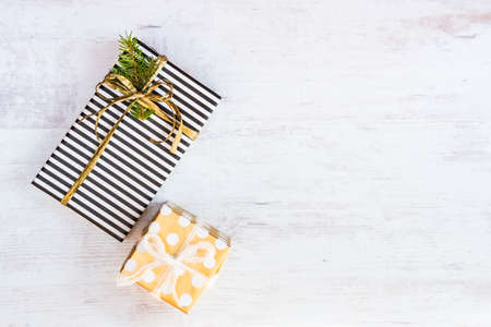 Gift boxes wrapped in black and white striped and golden dotted paper on a white wood background. Christmas presents. Empty space. Stock Photo