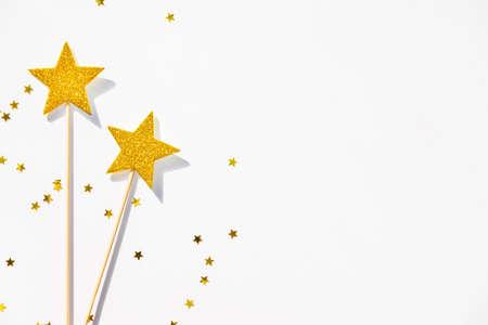 Zwei magische Zauberstäbe und Paillette der goldenen Partei auf einem weißen Hintergrund. Kopieren Sie Platz.