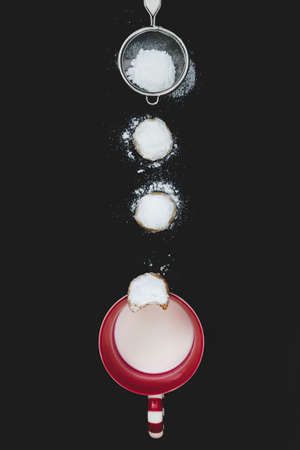 Homemade cookies covered with icing sugar, a sieve and a cup fo milk. Christmas baking abstract arrangement. Stock Photo