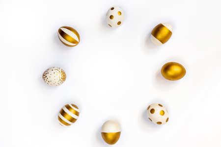 Top view of easter eggs colored with golden paint in differen patterns arranged in circle. Various striped and dotted designs. White background. Copy space.