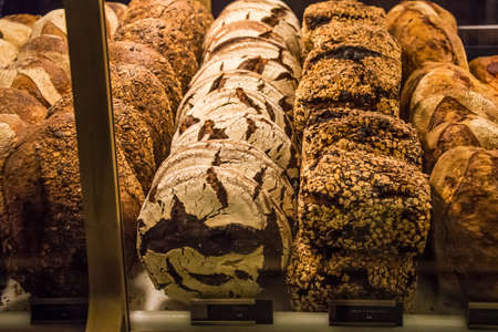 Variety of wholegrain breads arranged at a bakery window.