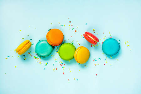 Top view of colorful macaroons and sugar sprinkles arranged over blue background.
