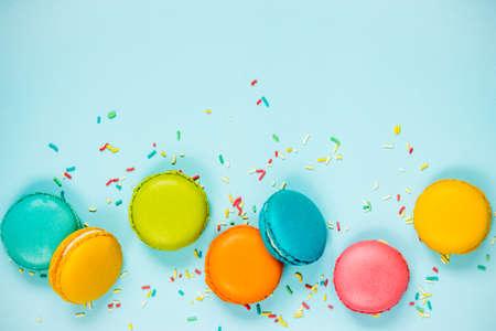 青色の背景に並べられたカラフルなマカロンと砂糖のスプリンクルのトップビュー。 写真素材 - 97420950