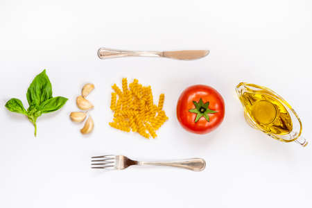 Top view of pasta ingredients and cutlery over white background - raw fusilli, fresh basil, garlic cloves, olive oil and ripe tomatoe. Italian food minimal concept. Stock Photo