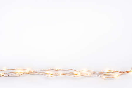 Christmas lights garland border over white background. Flat lay, copy space. Stockfoto