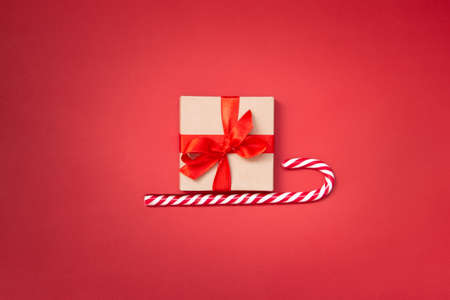Christmas sledge - a gift box over candy cane on a red background. Abstract christmas concept. Stockfoto
