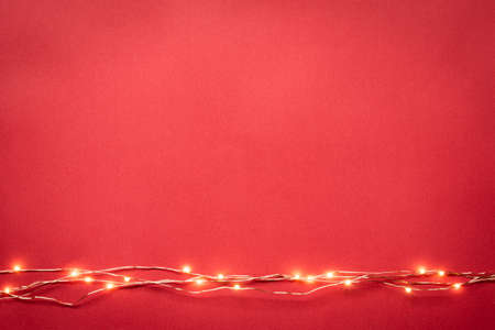 Christmas lights garland border over red background. Flat lay, copy space.
