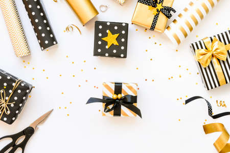 Top view of gift boxes and wrapping materials in various black, white and golden designs. A concept of Christmas, New Year, birthday celebration event. Stockfoto