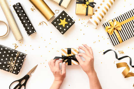 Top view of female hands wrapping gift boxes, scattered wrapping materials in various black, white and golden designs. A concept of Christmas, New Year, birthday celebration event. Stockfoto