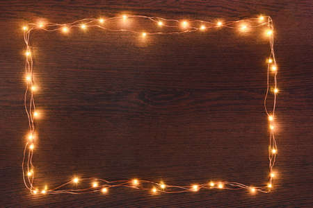 Christmas lights garland border over dark wooden background. Flat lay, copy space.