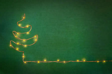 Christmas lights garland arranged like christmas tree over green background. Flat lay, copy space. Stockfoto
