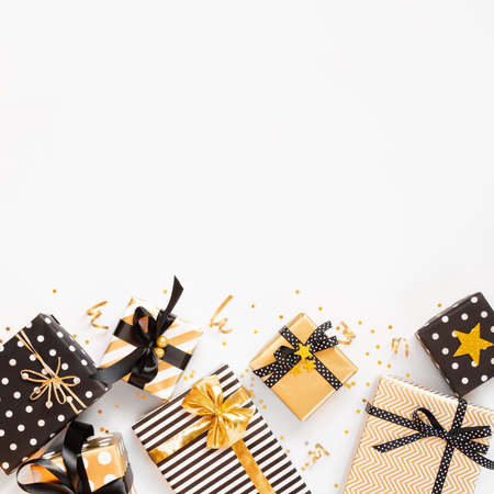 Top view of gift boxes in various black, white and golden designs. Flat lay, copy space. A concept of Christmas, New Year, birthday celebration event.