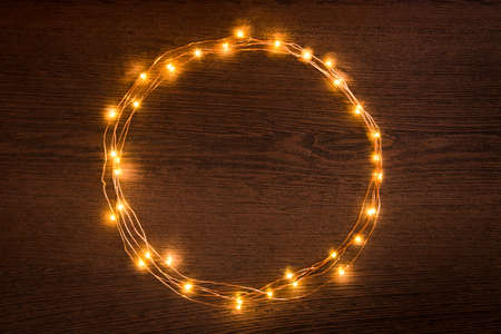 Christmas lights garland circular border over dark wooden background. Flat lay, copy space.