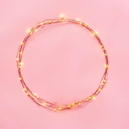 Christmas lights garland circular border over pink background. Flat lay, copy space.
