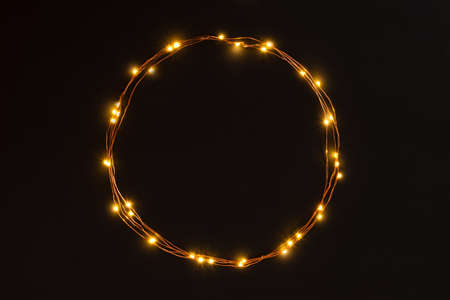 Christmas lights garland circular border over black background. Flat lay, copy space. Stockfoto