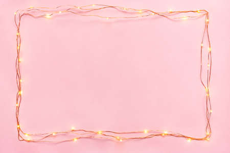 Christmas lights garland border over pink background. Flat lay, copy space. Stockfoto