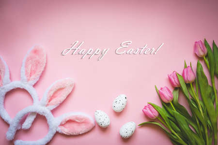 Top view of Easter eggs, pink tulips and two white fluffy bunny ears over pink background. Easter concept background. Happy Easter text.