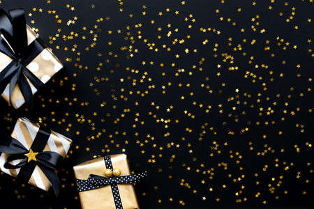 Gift boxes in various gold pattern wrapping papers over star shaped golden sequins on a black background. Stockfoto