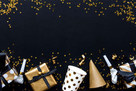 Gift boxes in various gold pattern wrapping papers and party accessories over star shaped golden sequins on a black background.
