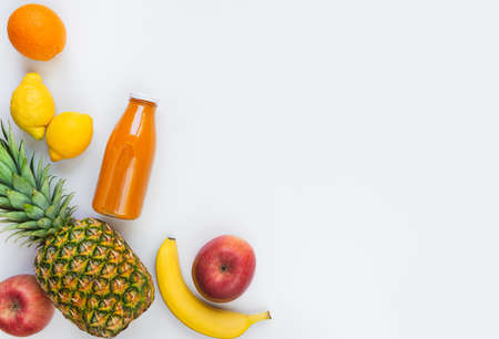Top view of various fruits and a bottle of freshly squeezed  multivitamin juice on a white background. Stockfoto