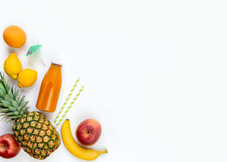 Top view of various fruits, a bottle of freshly squeezed multivitamin juice and cocktail accessories on a white background.