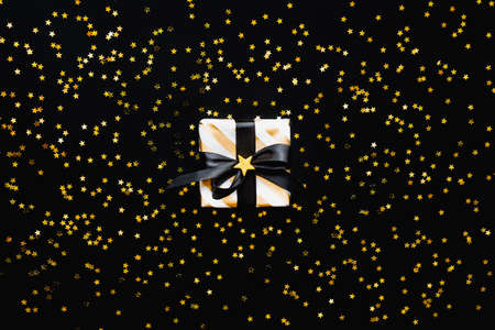 Star shaped golden sequins on a black background.