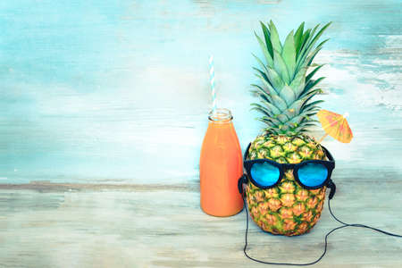 Pineapple with sunglasses and headphones and a bottle of juice in front of a blue wooden rustic background. Summer vacation party time concept.