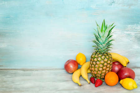A pile of fresh fruits in front of a blue rustic wooden background.