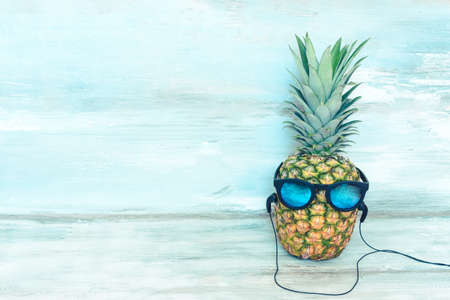 Ripe pineapple with blue mirror sunglasses and headphones in front of a blue wooden rustic background.
