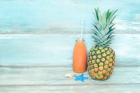 Summer concept stillife - ripe pineapple and a bottle of multivitamin juice in front of a blue rustic wooden background.