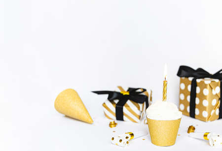 Cupcake with lighted candle and party accessories in golden color.