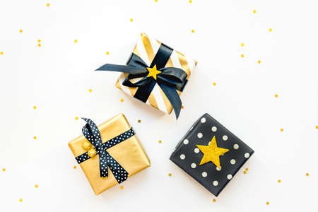 Top view of various gift boxes over star shaped golden sequins white background.
