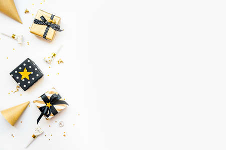 Top view of gift boxes and party accessories in various black, white and golden designs. Flat lay, copy space. A concept of Christmas, New Year, birthday celebration event.