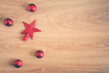 Christmas background - flat lay of red christmas balls over wooden background. Copy space.
