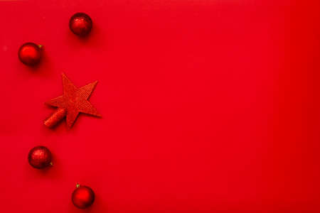 Christmas background - flat lay of red christmas star and balls over red background. Copy space. 写真素材