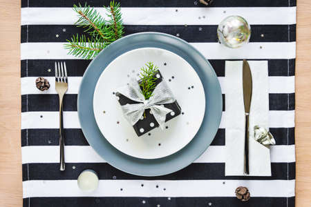Top view of christmas table setting. A gift box in a plate.