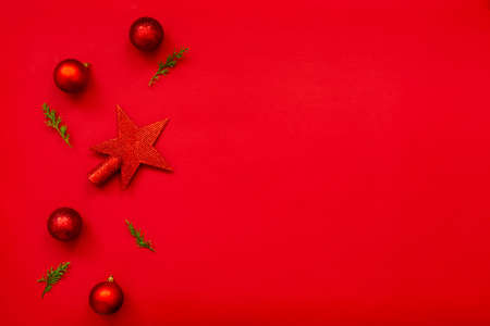 Christmas background - flat lay of red christmas balls, pine cones and fir branches over red background. Copy space.