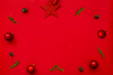 Christmas background - flat lay of red christmas balls, pine cones and fir branches arranged in circular frame over red background. Copy space. 写真素材