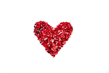 Valentine's Day concept - heart shaped confetti arranged like heart over white background.