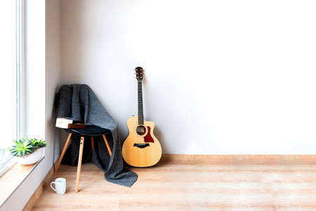 Contemporary home interior. Black chair covered with woolen gray blanket and acoustic guitar in front of an empty white wall. Time for hobby and leasure.